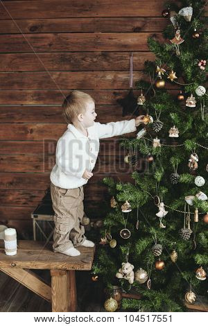 3 years old child is decorating Christmas tree, farm house design