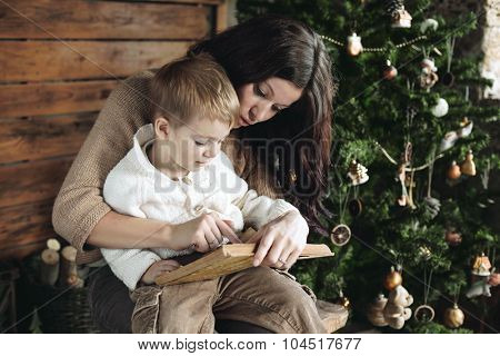 Mother with her 3 years old son reading book near Christmas tree, farm house design