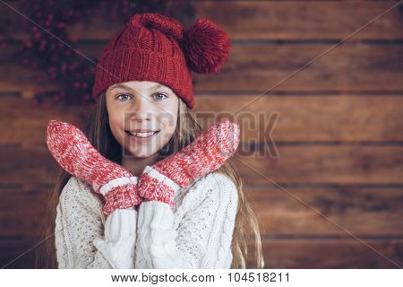 Child wearing knit clothing posing on rustic wooden background, Christmas decorated farmhouse interior.