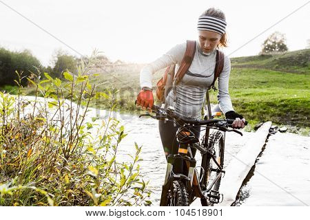 Lady with bicycle crossing the river with green coasts at sunset
