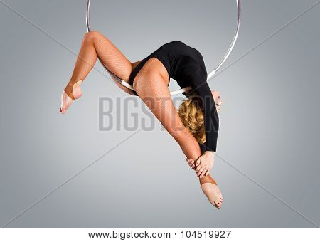 Plastic Beautiful Girl Gymnast On Acrobatic Circus Ring In Flesh-colored Suit. Aerial Ring.