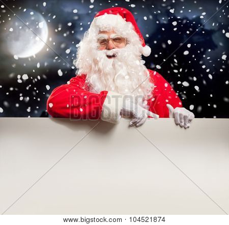 Santa Claus pointing to a blank sign with his finger