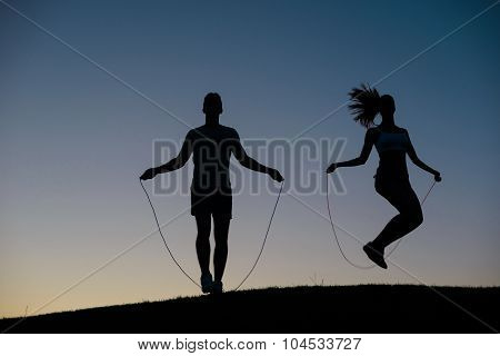 Guy with girl warming up on a skipping rope before the competiti