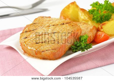 detail of grilled slices of pork and roasted potatoes