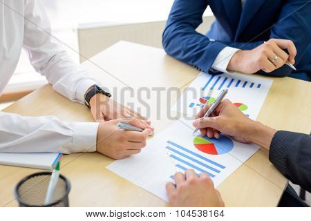 Business People Analyzing Financial Results on Graphs around the Table in Bright Modern Office. Team Work Concept