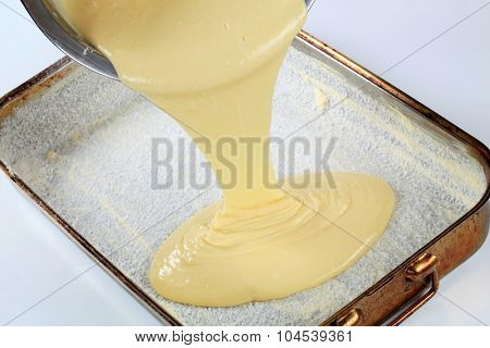 pouring batter into baking pan greased with butter and covered with coconut