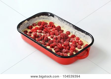 raw cake batter with frozen raspberries in baking tray ready to be baked