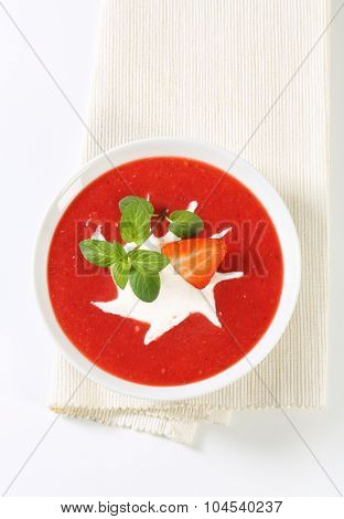 bowl of cold strawberry puree with cream on white place mat