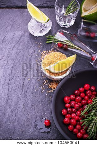 Ingredients for cranberry cocktail with lime and rosemary on a black stone