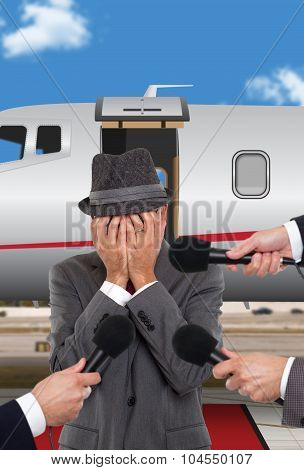 Businessman standing in front of corporate jet crying