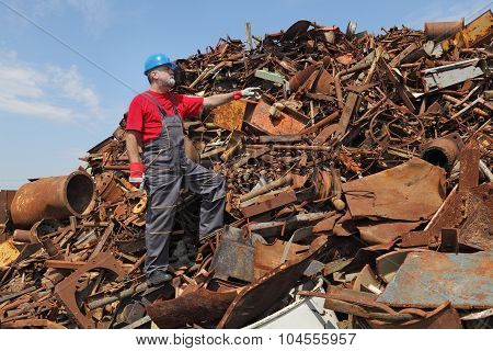 Recycling industry, worker gesture at heap of old metal