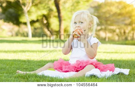 Cute Little Girl Sitting In Grass Eating Healthy Apple.