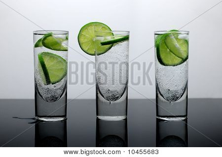Beverages. Fresh drink of water with lime and ice in three clear glasses on a reflective surface