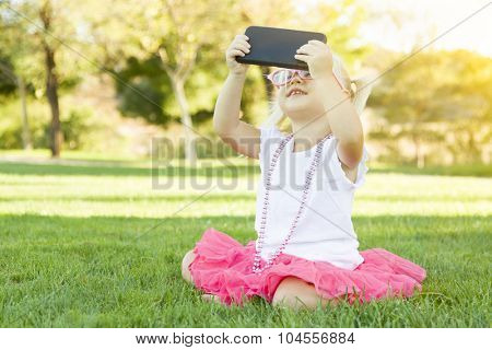 Cute Little Girl Sitting In Grass Taking Selfie With Cell Phone.