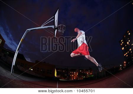 Basketball player slam dunking on an outdoor sports court