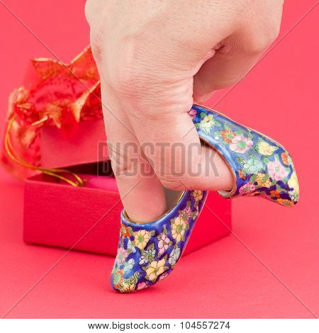Hand walking on porcelain shoes