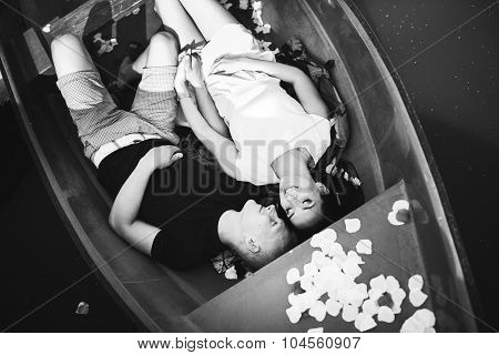 loving young couple are enjoying in the boat, rose petals