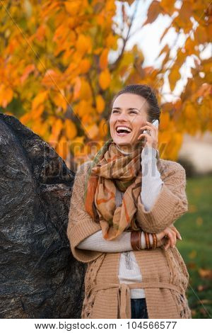 Young Woman Talking Cell Phone In Autumn Outdoors In Evening