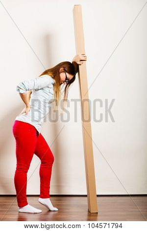 Tired Woman Moving Into Apartment Carrying Box.