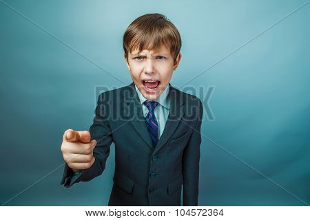 European appearance teenager boy in a business suit points a fin