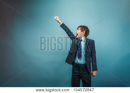 European appearance teenager boy in a business suit raised his h