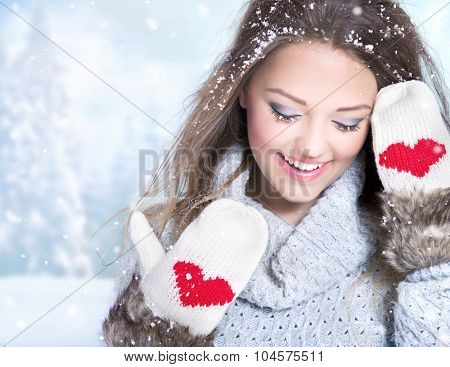 Beautiful happy smiling young woman wearing winter gloves covered with snow flakes. Christmas portrait concept. Winter landscape background