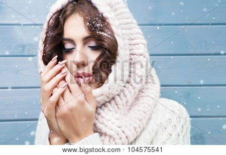 Winter portrait of young beautiful brunette woman with closed eyes wearing knitted snood covered in snow. Snowing winter beauty fashion concept.