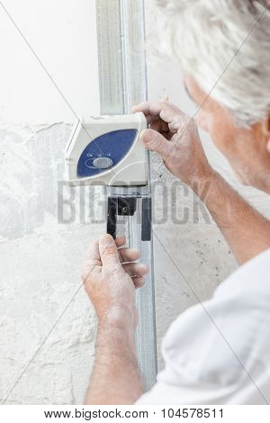 Builder using device on wall