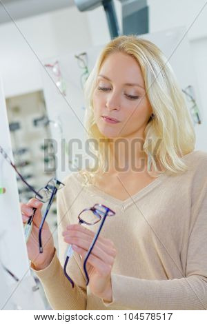 Lady holding two pairs of spectacles