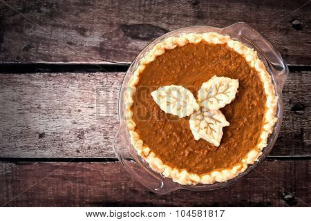 Pumpkin pie with leaf pastry toppings against rustic wood