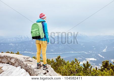 Back view of young woman wearing pink hat, blue jacket, green backpack, yellow pants and hiking boots standing against winter mountain valley - adventure concept