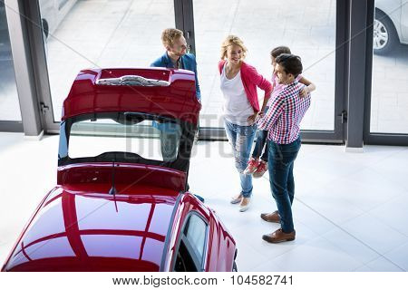 Car dealer offering a vehicle to young couple with daughter