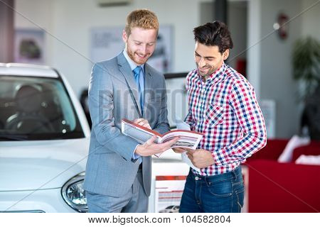 Male Caucasian salesman and male client at the car dealership saloon indoors
