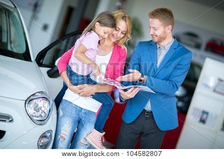 Young smiling mom holding her daughter in car showroom