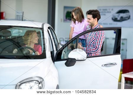 Happy young  family  chooses to buy a car at the car dealership saloon