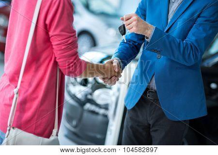 Buy new car,   woman receiving car key from salesman