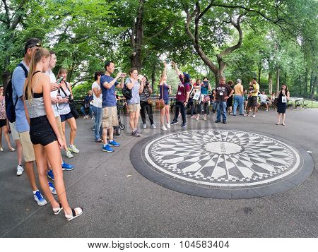 NEW YORK,USA - AUGUST 21,2015 : Tourists at the Imagine mosaic commemorating John Lennon at Strawberry Fields in Central Park