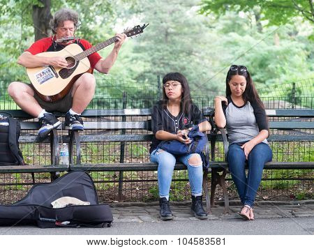 NEW YORK,USA - AUGUST 21,2015 : Street performer singing John Lennon songs at Strawberry Fields in Central Park