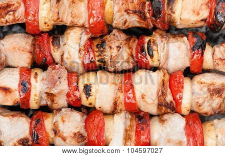 Smoky grilled marinated meat skewers pork with tomatos and onion. Close up