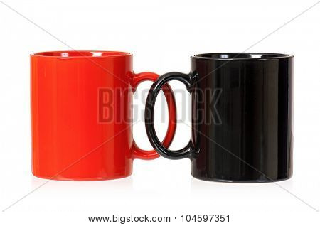 Two cups for coffee or tea - red and black, isolated on white background