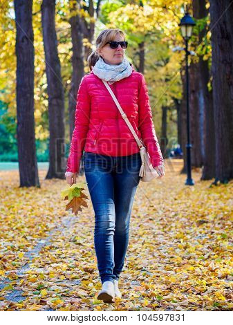 Middle age woman walking in city park