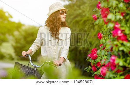Sexy woman with vintage bike in a country garden