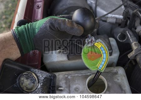 Mechanic Checking Strength Of Antifreeze