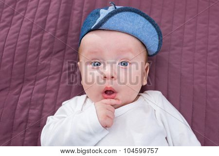 Baby boy in hat posing at the camera