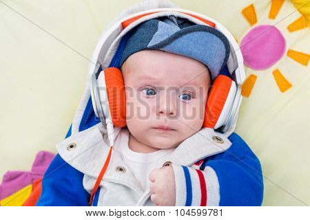 Baby boy in hat listening to the music on headphones