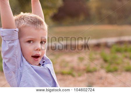 toddler boy wearing nice purple shirt playing at a playground
