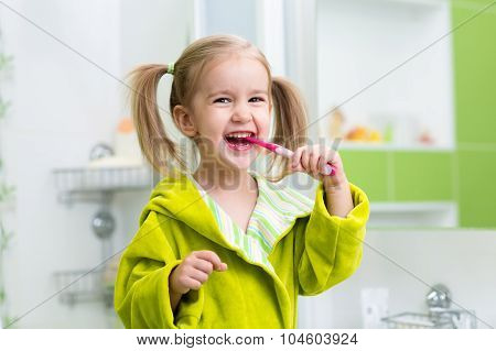 Smiling little girl brushing teeth in bathroom