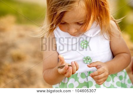 Little Girl Holding Her Hand On The Small Green Lizard.