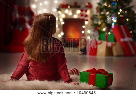 Cute child looking at the decorated christmas tree
