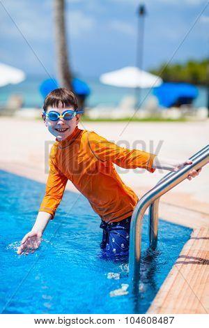 Cute boy wearing sun protection swimwear at pool